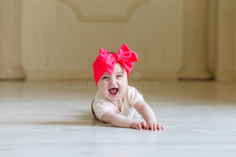 Cute happy 6 months baby girl with bright bow crawling indoor. Pretty smiling baby girl with open mounth. Light royalty free stock image
