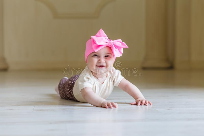 Cute happy 6 months baby girl with bright bow crawling indoor. Pretty smiling baby girl with open mounth. Light stock images