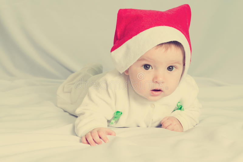 Cute happy newborn baby in christmas hat royalty free stock photos