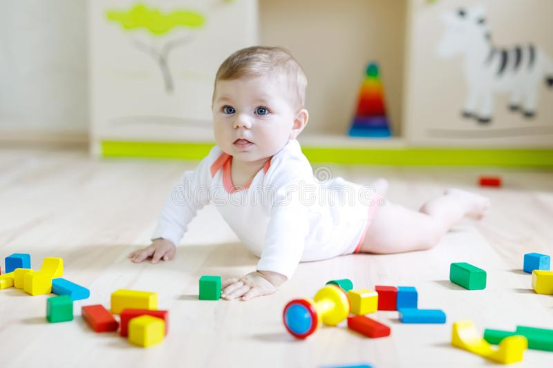 Cute baby girl playing with colorful rattle toys. Cute happy smiling baby playing with colorful rattle toys. New born child, little girl learning crawling stock image