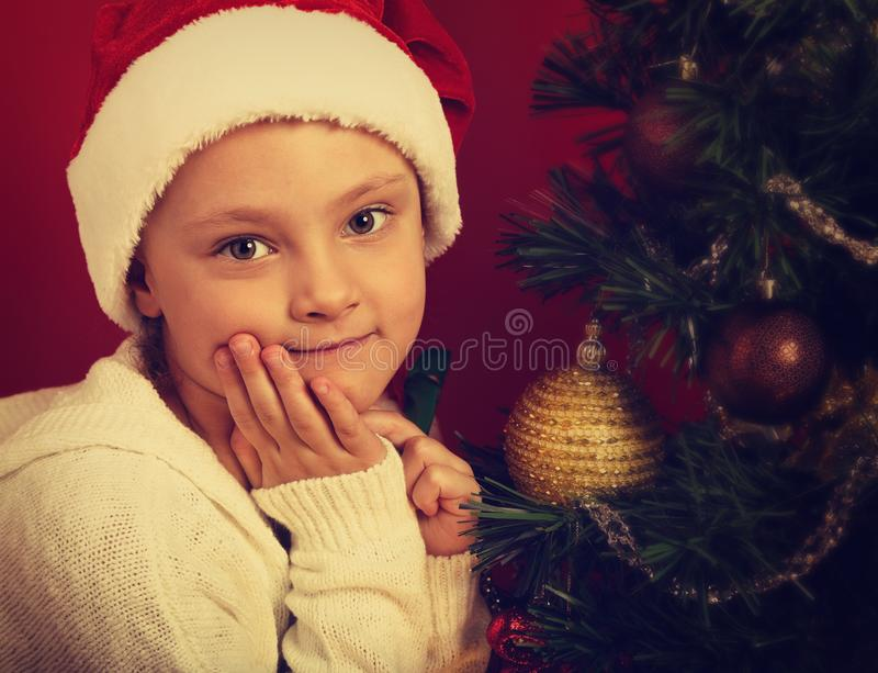 Cute happy smiling girl in fur santa claus hat near the Christmas holiday tree with toys looking. Closeup bright portrait stock photos