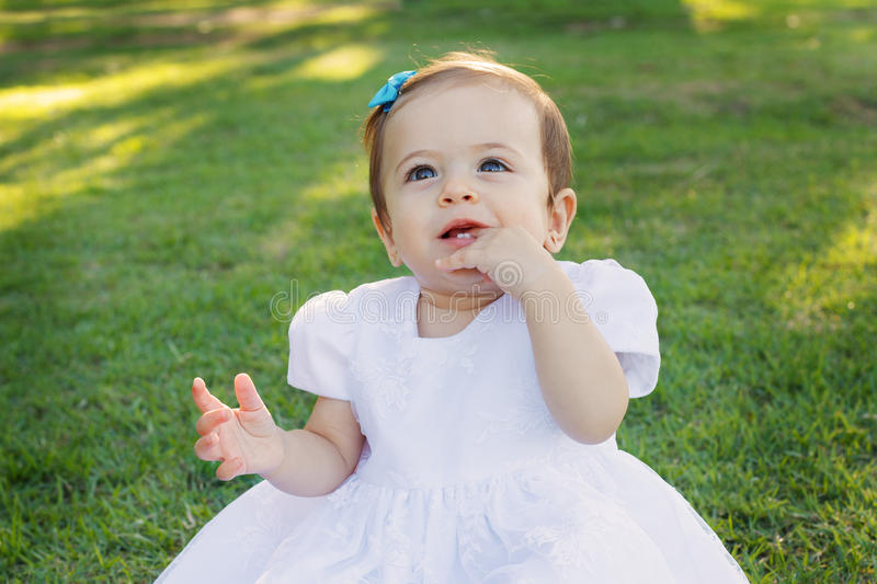 Cute happy smiling little baby girl in white dress scratching first teeth royalty free stock photos