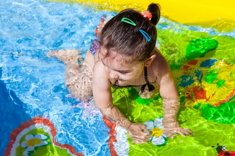 Cute, happy, smiling toddler baby girl, swimming, and playing in colorful inflatable. Backyard swimming pool on hot summer day. Thirteen months old royalty free stock photos