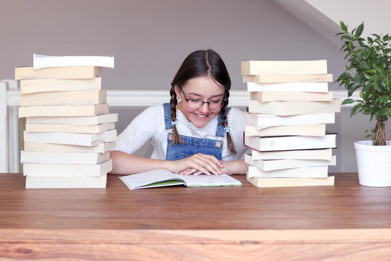 Cute happy smiling tween girl in glasses studying reading book sitting a table with pile of books at home. royalty free stock photo