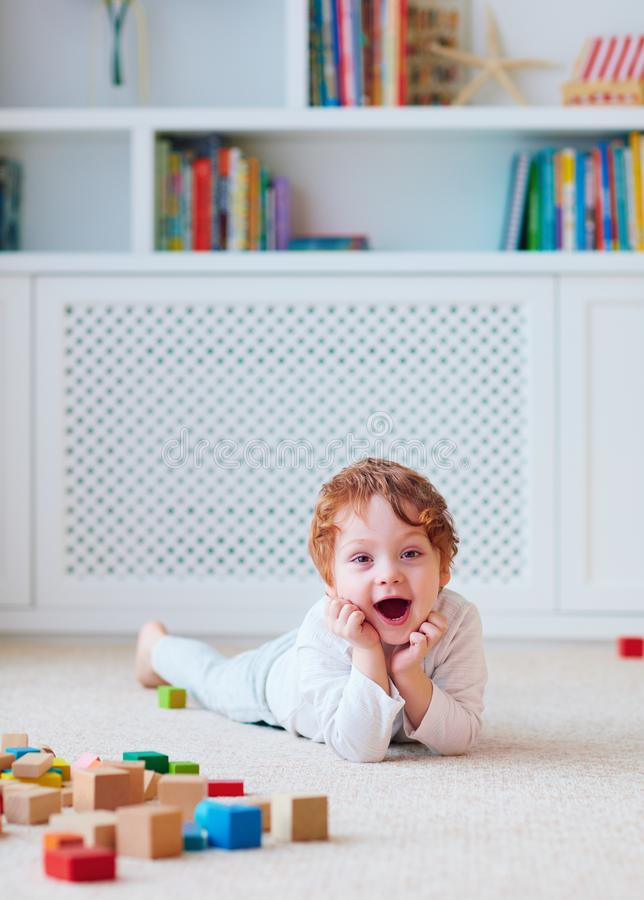 Cute toddler baby boy playing with wooden blocks on the carpet royalty free stock photos