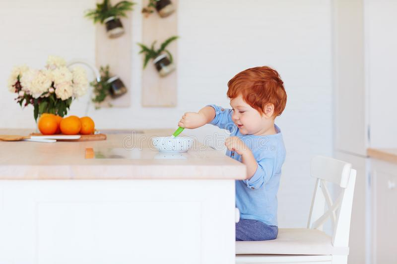Cute happy toddler baby boy sitting at the table, having breakfast in the morning royalty free stock photo