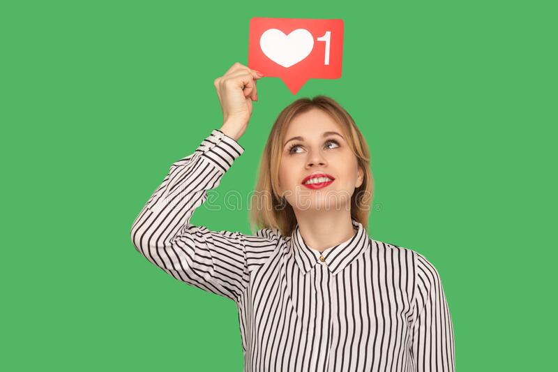 Cute happy woman with red lips in glamour striped blouse holding social media heart Like icon over head. Recommending to follow blog, love trendy content royalty free stock photo