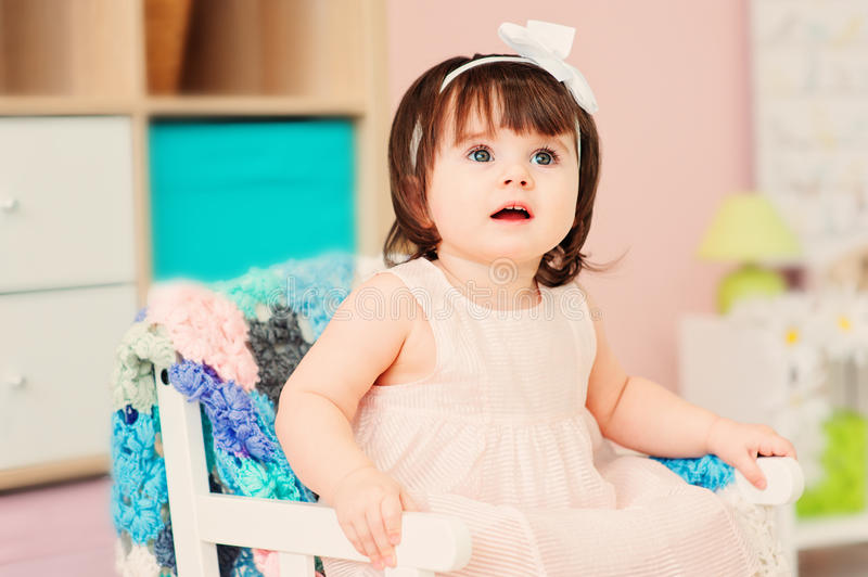 Cute happy 1 year old baby girl playing with wooden toys at home stock photo