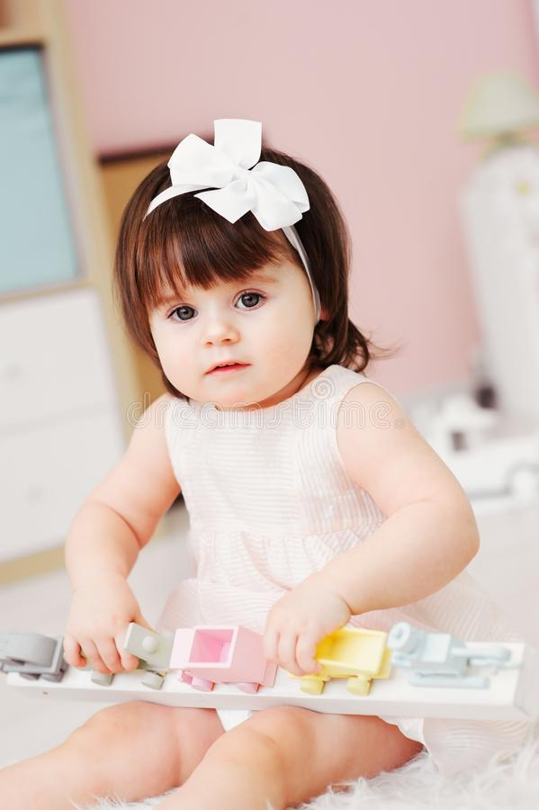Cute happy 1 year old baby girl playing with wooden toys at home stock photography