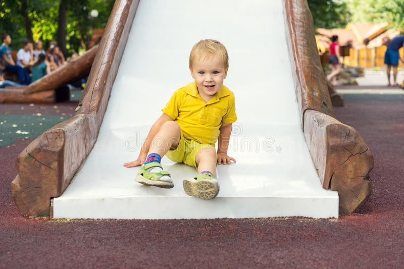 Cute happy 2 year old boy riding slide in an outdoor playground on vacation stock images