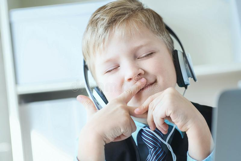 Cute happy 6 year old boy in suit listening to music or audio tutorial on headphones at the office background. Little boy in suit listening to music on stock photo