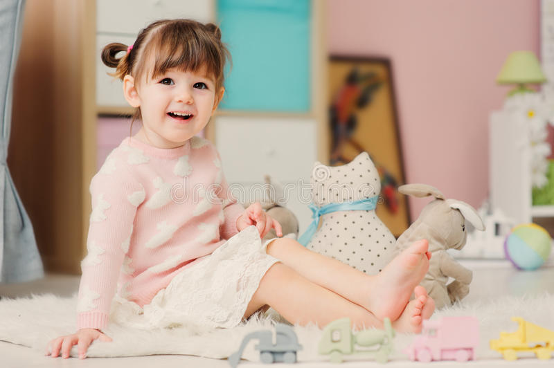 Cute happy 2 years old baby girl playing with toys at home. Modern nursery interior in pastele tones, early learning concept royalty free stock images
