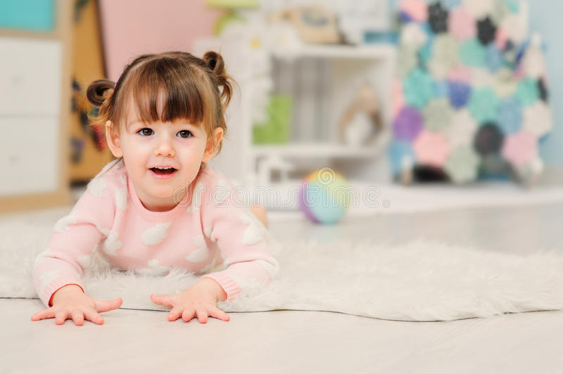 Cute happy 2 years old baby girl playing with toys at home. Modern nursery interior in pastele tones, early learning concept royalty free stock photo