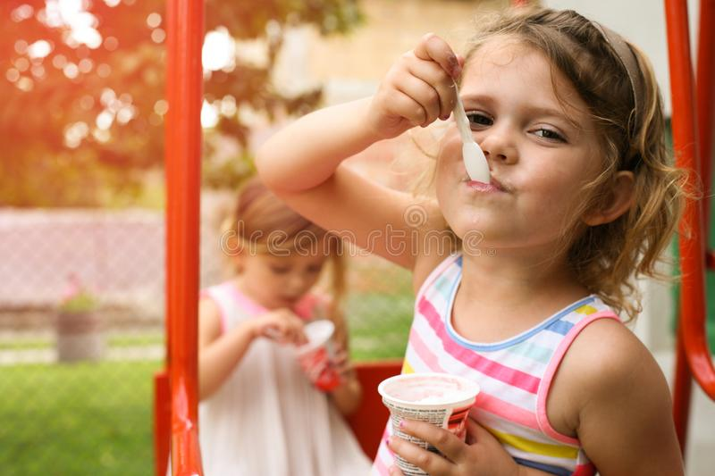 Little girls eating ice cream outside. royalty free stock photography