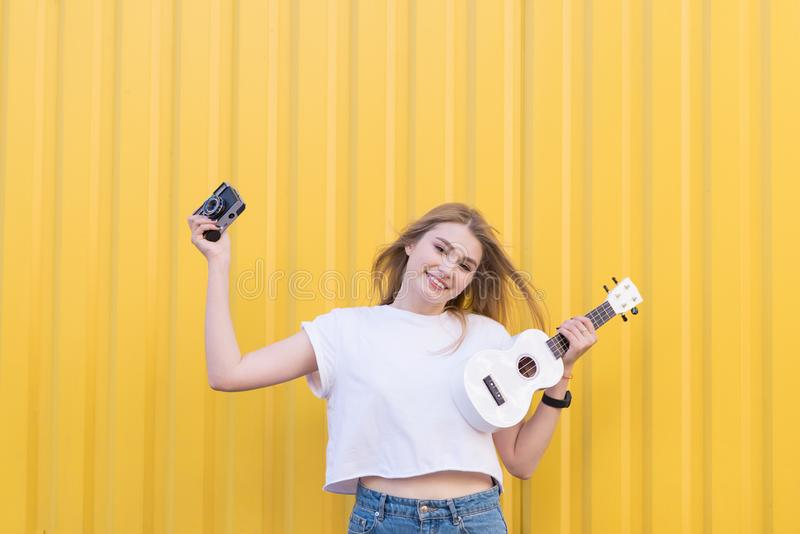 happy young model posing with white ukulele and retro camera on background of yellow wall stock photo