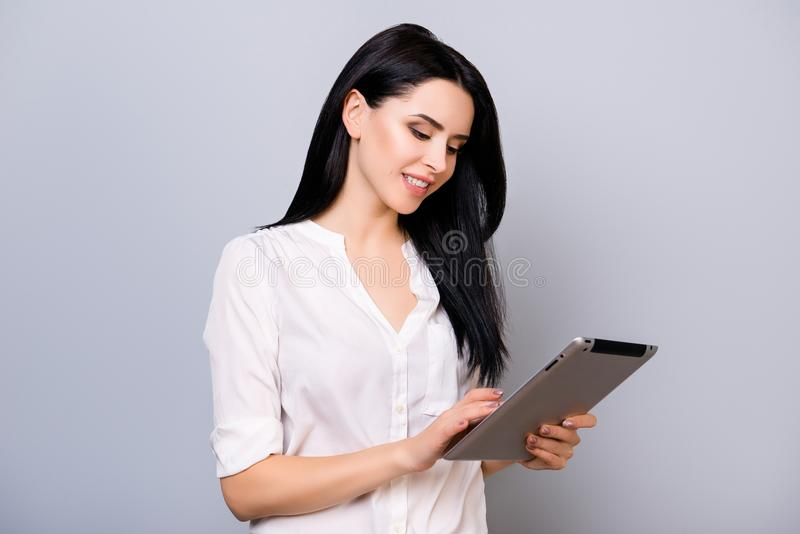 Cute happy young woman using digital tablet with toothy smile wh royalty free stock photo