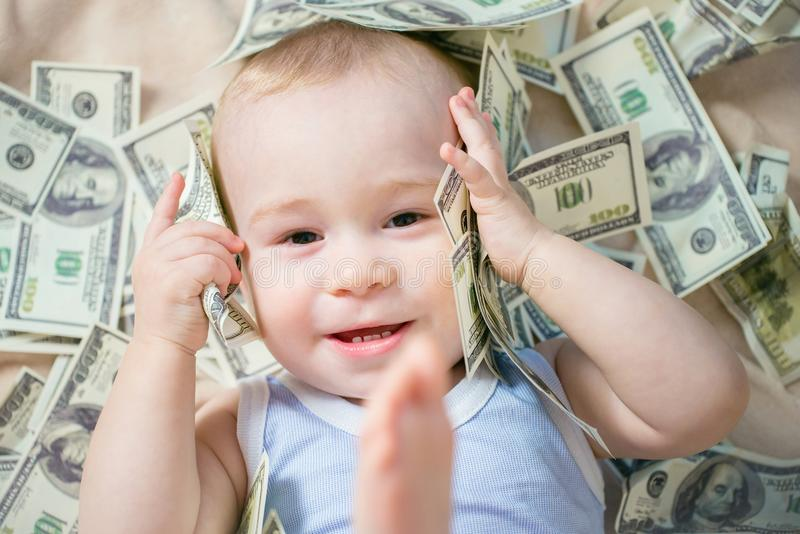 Cute hapy baby boy playing with a lot of money, american hundred dollars cash stock photo