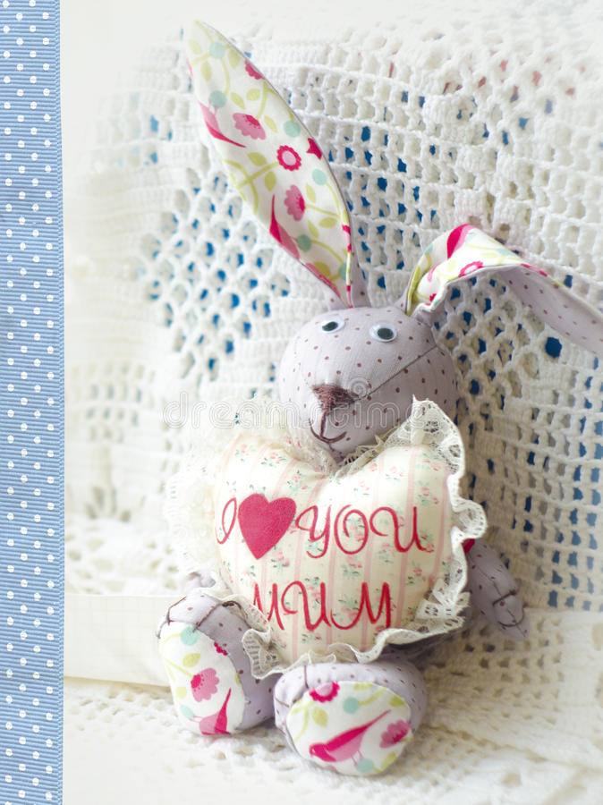 Cute hare. Happy Mother's Day bunnie holding heart with the inscription I love mum. Greeting card for Mother's day royalty free stock photography