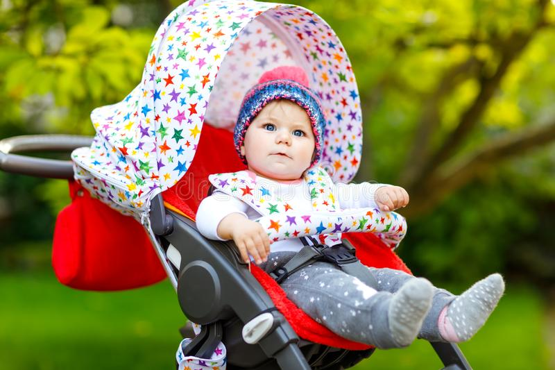Cute healthy little beautiful baby girl with blue warm hat sitting in the pram or stroller and waiting for mom. Happy. Smiling child with blue eyes. baby stock photography