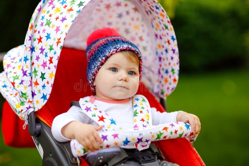 Cute healthy little beautiful baby girl with blue warm hat sitting in the pram or stroller and waiting for mom. Happy. Smiling child with blue eyes. baby stock images