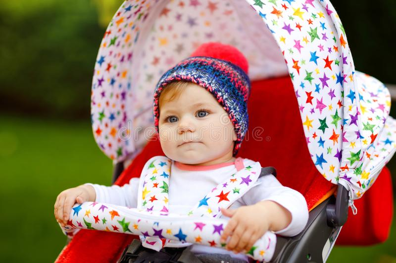 Cute healthy little beautiful baby girl with blue warm hat sitting in the pram or stroller and waiting for mom. Happy. Smiling child with blue eyes. baby royalty free stock photos