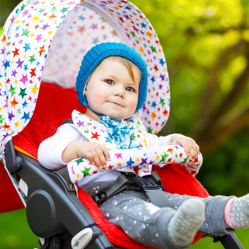 Cute healthy little beautiful baby girl with blue warm hat sitting in the pram or stroller and waiting for mom. Happy. Smiling child with blue eyes. baby royalty free stock photography