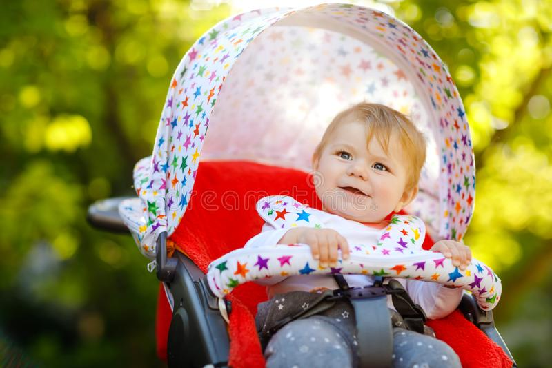 Cute healthy little beautiful baby girl sitting in the pram or stroller and waiting for mom. Happy smiling child with. Blue eyes. With green tree background royalty free stock photos