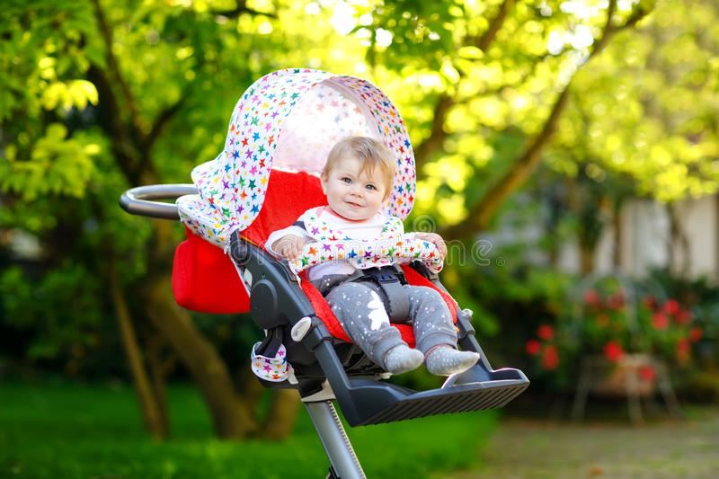 Cute healthy little beautiful baby girl sitting in the pram or stroller and waiting for mom. Happy smiling child with. Blue eyes. With green tree background royalty free stock images