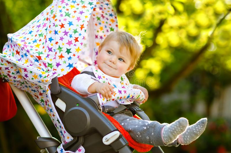 Cute healthy little beautiful baby girl sitting in the pram or stroller and waiting for mom. Happy smiling child with. Blue eyes. With green tree background royalty free stock photo