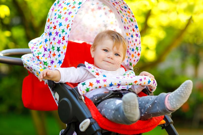 Cute healthy little beautiful baby girl sitting in the pram or stroller and waiting for mom. Happy smiling child with. Blue eyes. With green tree background stock photo