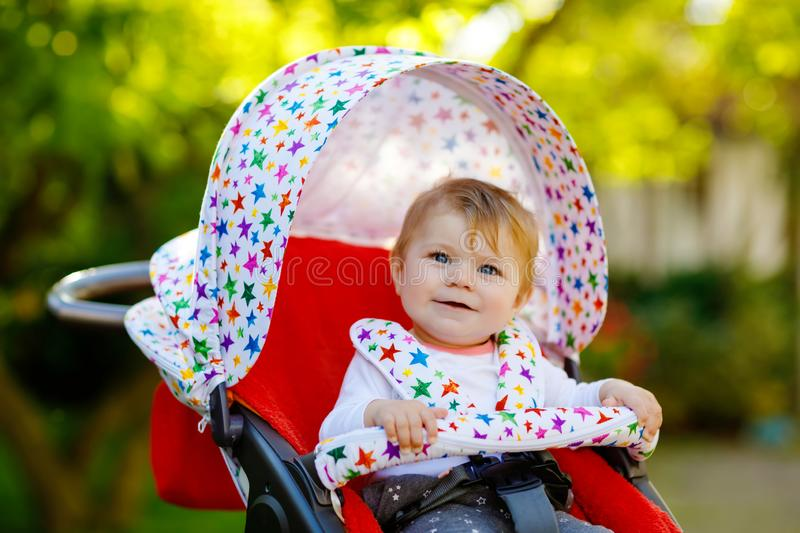 Cute healthy little beautiful baby girl sitting in the pram or stroller and waiting for mom. Happy smiling child with stock photos