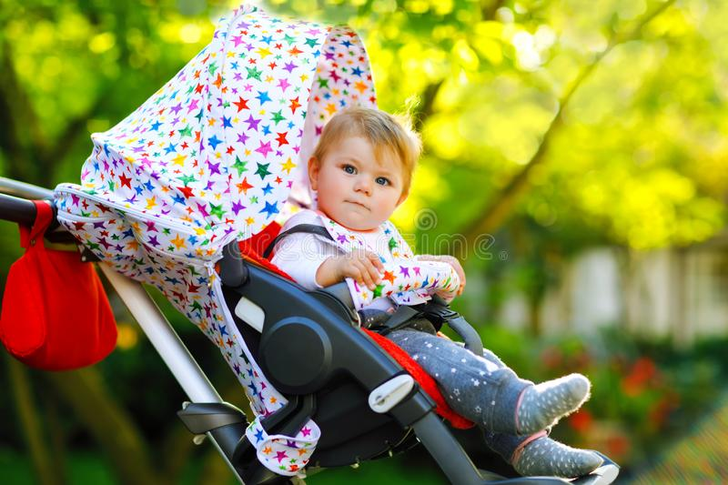 Cute healthy little beautiful baby girl sitting in the pram or stroller and waiting for mom. Happy smiling child with. Blue eyes. With green tree background stock photography