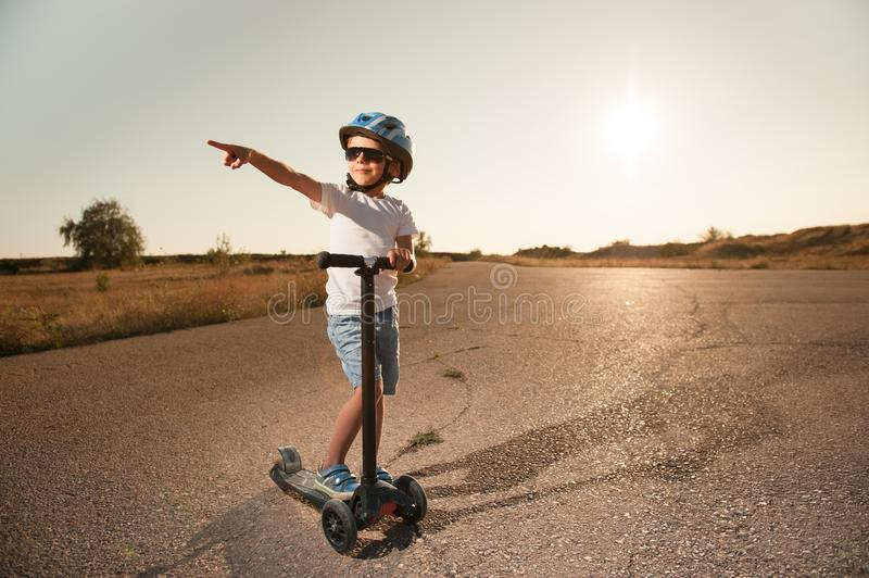 Cute healthy little boy in sunglasses and sport helmet with scooter on road royalty free stock image