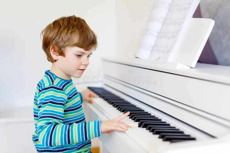 Cute healthy little kid boy playing piano in living room or music school. Preschool child having fun with learning to. Play music instrument. Education, skills royalty free stock photography