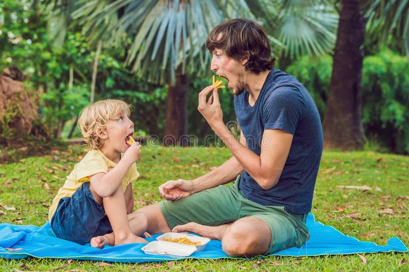 Cute healthy preschool kid boy eats french fries potatoes with k. Etchup with his father. child eating unhealthy food. Mom was upset stock photos