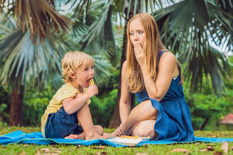 Cute healthy preschool kid boy eats french fries potatoes with ketchup with his mom. child eating unhealthy food. Mom was upset royalty free stock photos