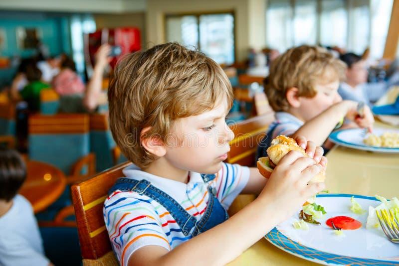 Cute healthy preschool kid boy eats hamburger sitting in school or nursery cafe. Happy child eating healthy organic and stock photo