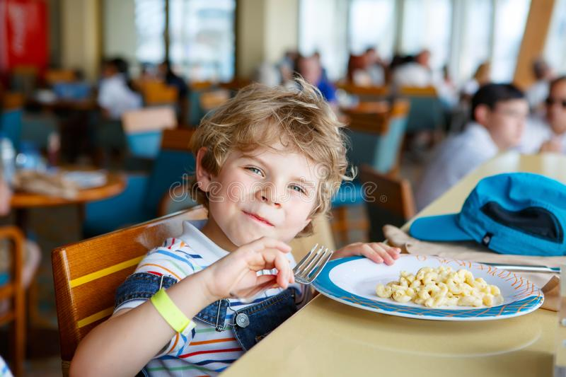 Cute healthy preschool kid boy eats pasta noodles sitting in school or nursery cafe. Happy child eating healthy organic. And vegan food in restaurant. Childhood stock photos