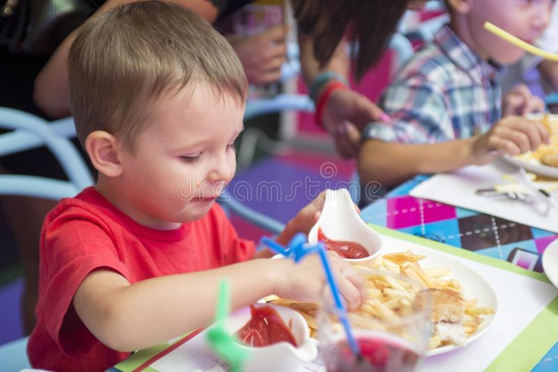 Cute healthy preschool kid boy eats sitting in school or nursery cafe. Happy child eating healthy organic and vegan food in restau royalty free stock photography