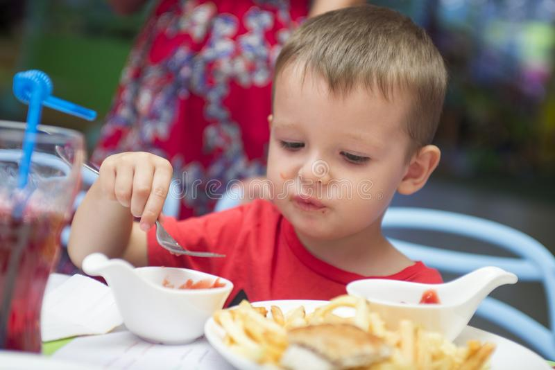 Cute healthy preschool kid boy eats sitting in school or nursery cafe. Happy child eating healthy organic and vegan food in restau. Rant. Childhood, health stock photos
