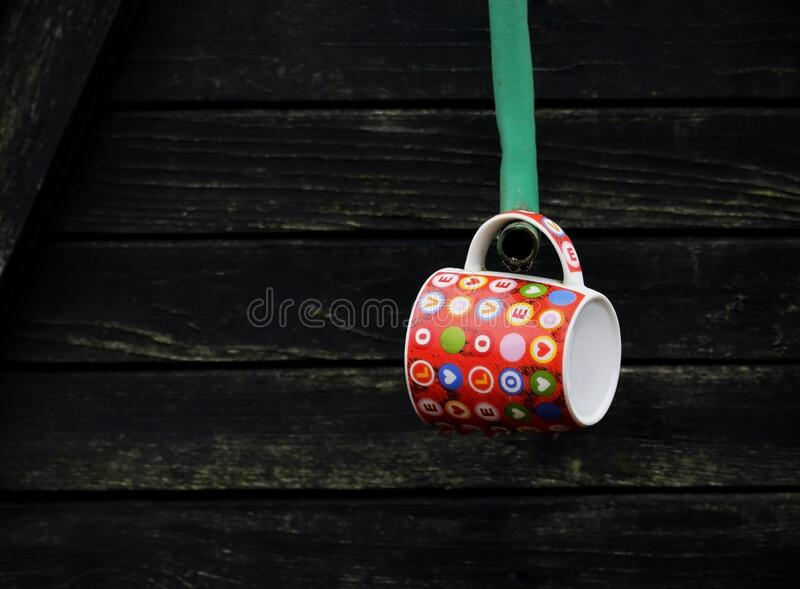 Cute heart design cup hanging on metal handle of country well. Cute heart design cup hanging on metal handle of wooden country well stock image