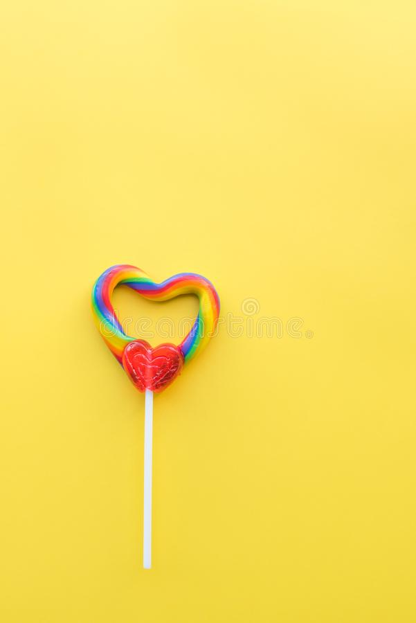 Cute heart-shaped rainbow swirl lollipop on solid yellow background portrait format stock photography