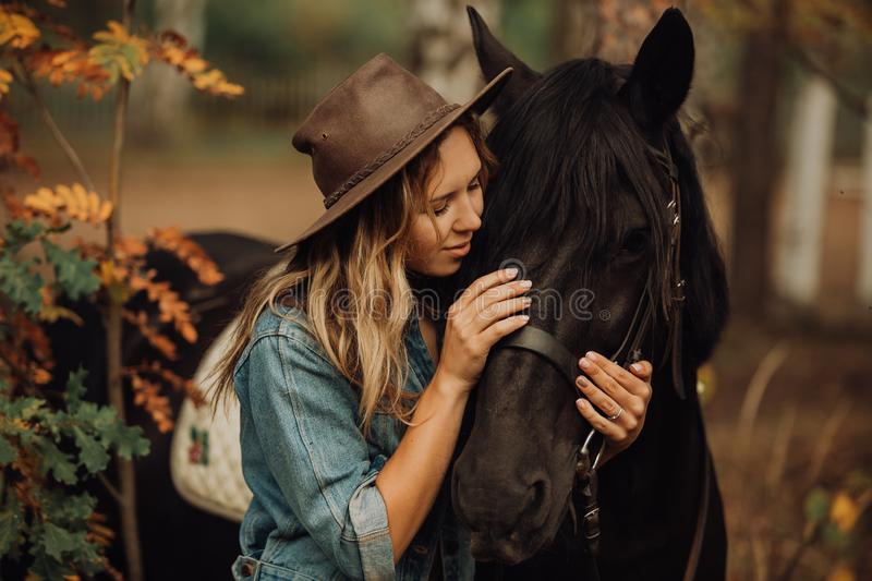 Hipster girl with a horse in the woods smiling stock images