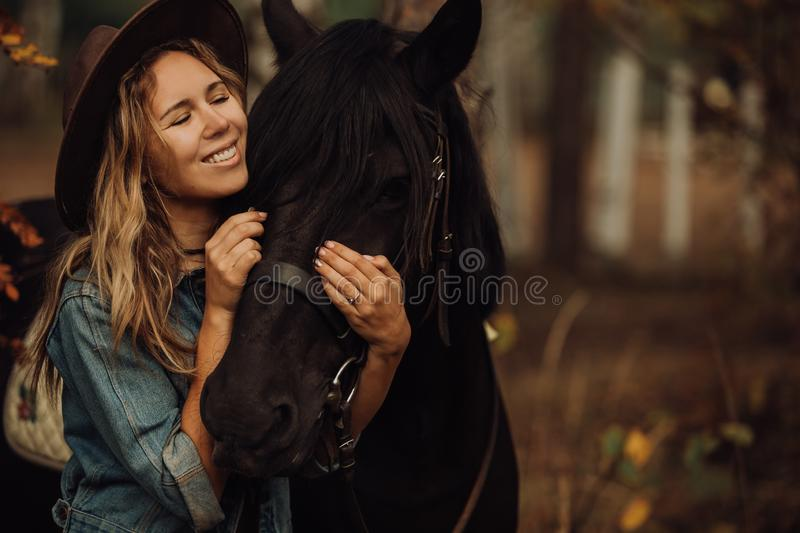 Hipster girl with a horse in the woods smiling stock image