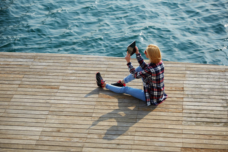 Cute hipster girl relaxing at her sunny holiday photographing outdoors,. High angle shot of young tourist woman taking a photo of a beautiful view with her stock photography