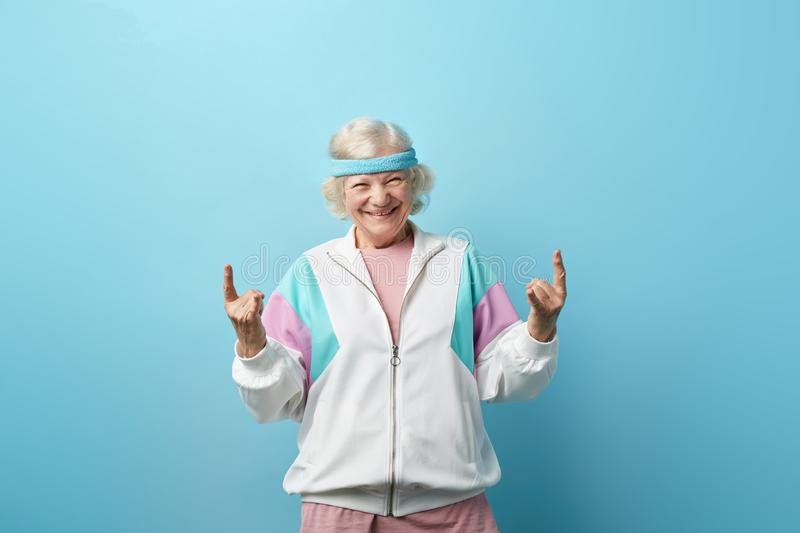 Cute hipster grandmother smiling and making rock sign against blue background stock photos
