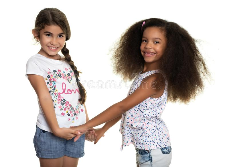 Cute hispanic and african-american small girls holding hands. Isolated on white stock photos