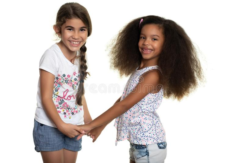 Cute hispanic and african-american small girls holding hands. Isolated on white stock photo
