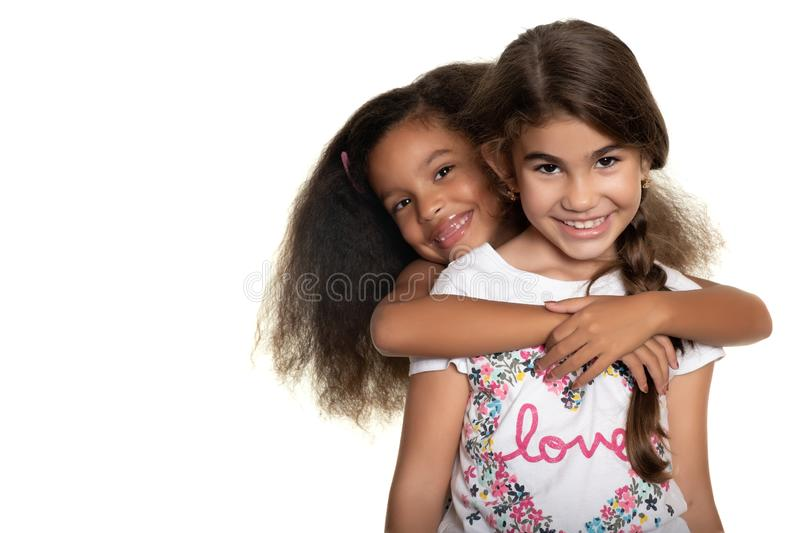 Cute hispanic and african-american small girls hugging. With a smile - Isolated on white stock images
