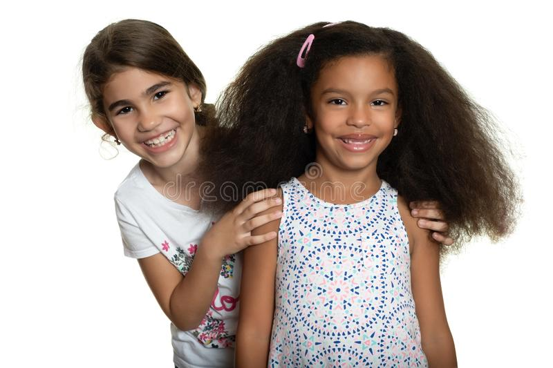 Cute hispanic and african-american small girls hugging. With a smile - Isolated on white stock photos
